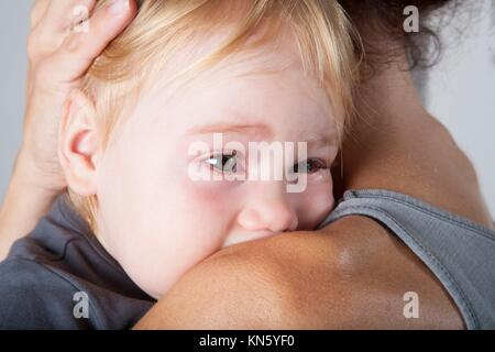 portrait of one year age blonde lovely cute caucasian white baby grey shirt looking face crying and scream shout - Stock Photo