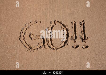 go word written on brown sand ground low tide beach ocean seashore in Spain Europe. - Stock Photo