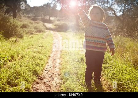 Little girl hold a dry stem as a magic wand against the sun on dehesa landscape, Extremadura, Spain. - Stock Photo
