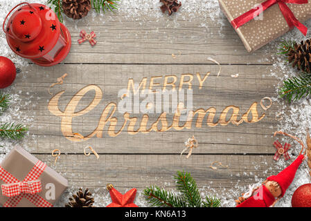 Creative hand carved Merry Christmas text in a wooden surface. Surrounded with Christmas decorations. Top view of - Stock Photo