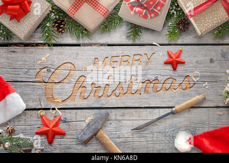Christmas hand craft on wooden surface with hammer and chisel. Wooden carving greeting text surrounded with gifts - Stock Photo