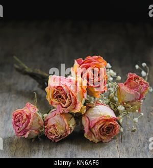 Dried rose on wooden table. - Stock Photo