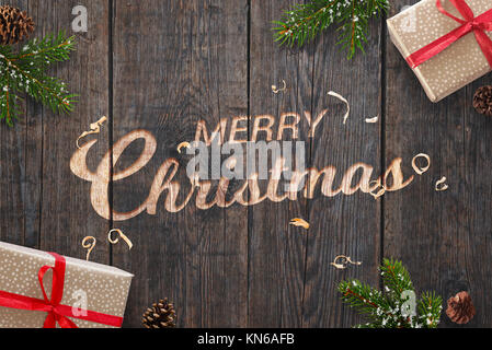 Christmas greeting text hand carved on dark wooden surface with Christmas decorations. Gifts, fir branches and pinecones - Stock Photo