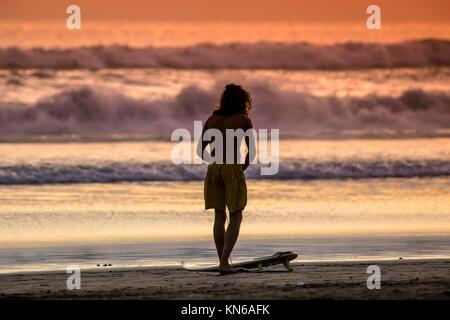Surfer on the Beach at Sunset Tme, Bali, Indonesia. - Stock Photo