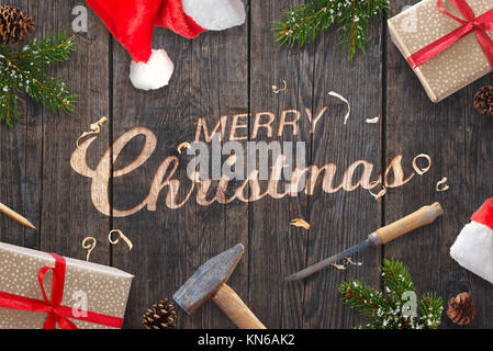 Santa Claus hand carved Merry Christmas text on wooden surface with chisel and hammer. Fir branches, presents and - Stock Photo