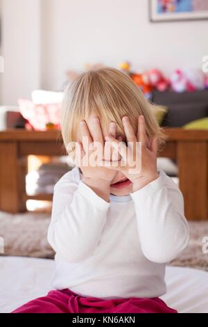 portrait of blonde caucasian baby nineteen month age covering her face with two hands white shirt. - Stock Photo