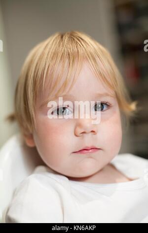 portrait of blonde caucasian baby nineteen month age chubby face looking at camera with serious expression. - Stock Photo