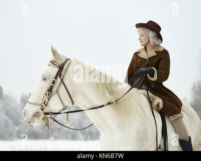 Attractive woman wearing winter jacket and hat, she riding a white horse. South Finland in February. - Stock Photo