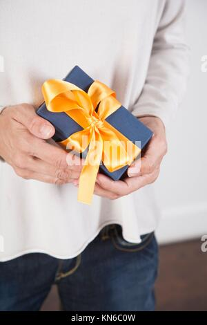 blue gift box with yellow ribbon in woman blue jeans cream jersey hands over white background. - Stock Photo