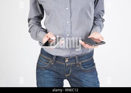woman blue jeans trousers and grey shirt with mobile phone smartphone blank screen in her both two hands isolated - Stock Photo
