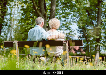 Romantic elderly couple sitting together on a bench in a tranqui - Stock Photo