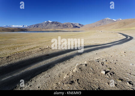 Lonely road in the deserted landscape at Tso Kyagar with a panoramic view over the himalayan mountains, Ladakh, - Stock Photo
