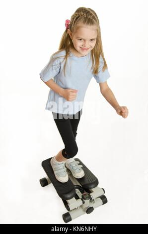 Six year old girl Europeans engaged in physical exercises. - Stock Photo