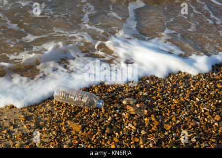 A clear plastic empty 500ml bottle on a shingle beach with waves lapping around it. - Stock Photo