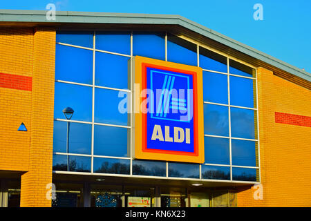 The logo and store sign of the Aldi supermarket in Talbot Green. Warm brickwork and blue sky. South Wales UK. - Stock Photo