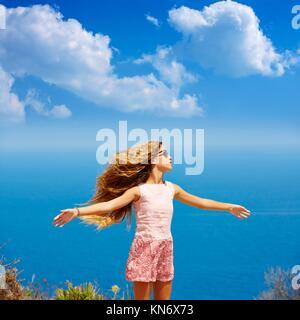 Blond girl shaking hair on air at blue Mediterranean sea tourist in Spain open hands.