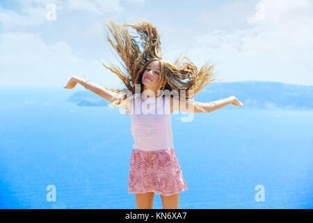 Blond girl shaking hair on air at blue Mediterranean sea tourist in Spain.