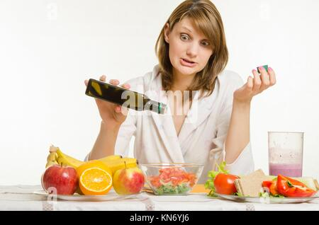 Young beautiful girl in a bathrobe prepares vegetarian salad from vegetables and greens isolated on white background. - Stock Photo