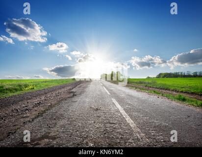 Asphalted highway in the field and sunlight. - Stock Photo