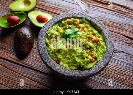 avocado Guacamole on molcajete real Mexican traditional procedure. - Stock Photo