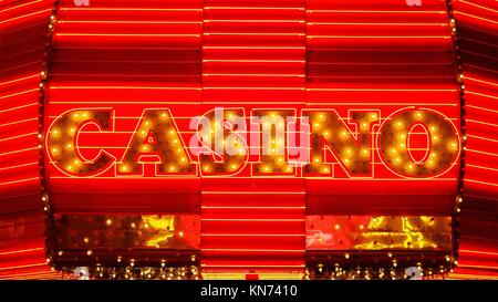 The word casino is lit up in neon lights at night on Freemont Street in Las Vegas. - Stock Photo