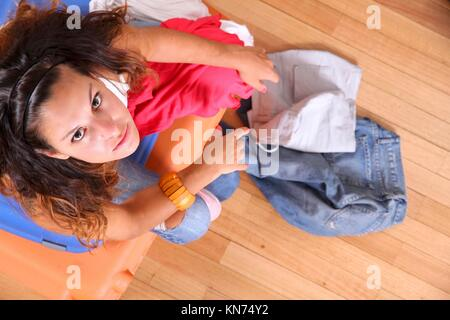 A young woman sitting on a stack of suitcases with too much clothes to fit in. - Stock Photo