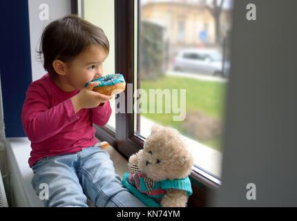 little girl and her bear toy eating donuts. - Stock Photo