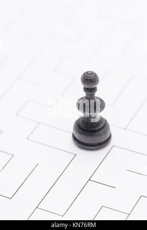 Black chess piece standing in blank maze. Conceptual image of business solution, office strategy and finding the - Stock Photo