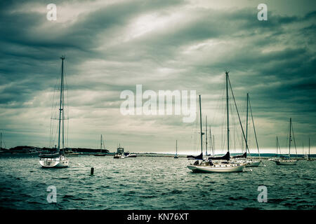 Nautical scene of anchored sailboats under storm clouds - Stock Photo