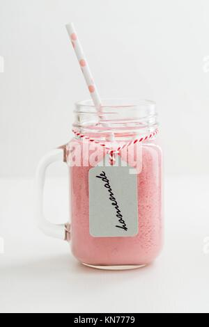 Healthy pink smoothie with berries and yogurt in a glass with handwritten homemade label. - Stock Photo