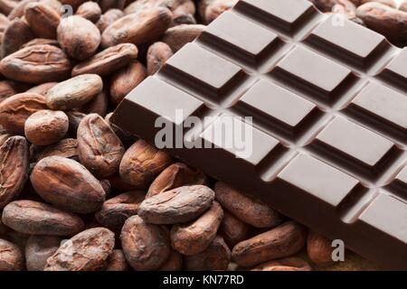 Bar of chocolate with raw cocoa beans. - Stock Photo