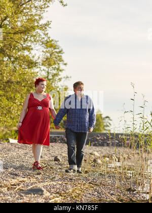 Lovely couple walking on the shoreline, warm summer evening light. - Stock Photo