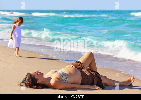 Beautiful pregnant woman on the beach lying with daughter. - Stock Photo