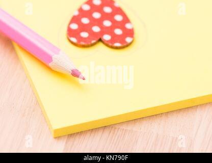 Office romance. Heart on post-it memo note on desktop in workplace. - Stock Photo