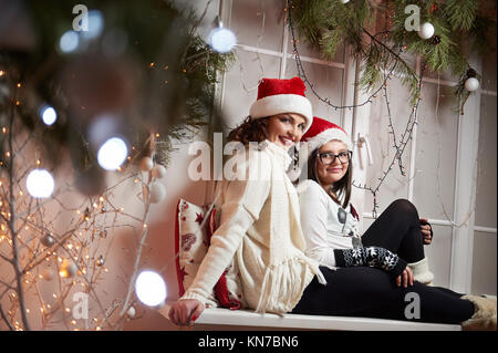 Happy mother and daughter sitting on a windowsill on Christmas e - Stock Photo