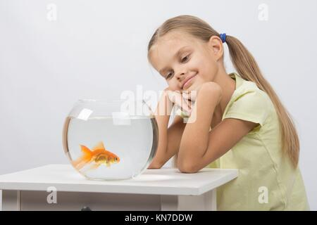 Happy six year old girl sits at a table at the fishbowl with goldfish. - Stock Photo