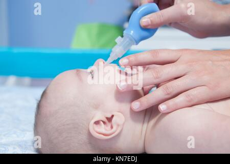 Mother using baby nasal aspirator. She is doing a mucus suction to three months baby boy. - Stock Photo