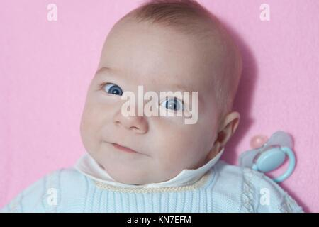 Awake four month baby boy lying in cot with dummy out. Overhead view. - Stock Photo