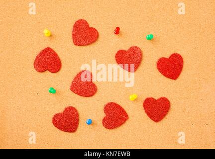 Hearts on noticeboard. Symbol of love, valentine holiday and office romance. - Stock Photo