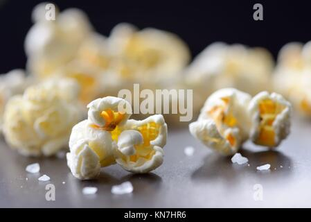 Popcorn and salt isolated on black background. - Stock Photo