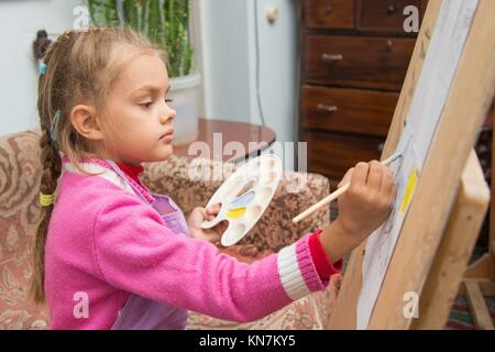 Five-year girl with a brush paints a picture on an easel and holding in his other hand in the artist's palette. - Stock Photo