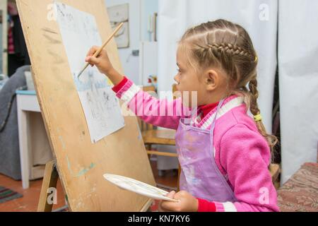 Five-year girl with a brush paints a picture on an easel and holding in his other hand in the artists palette. - Stock Photo