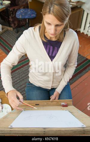 A young girl draws a pencil on the easel with a portrait sculpture in the artists studio. - Stock Photo