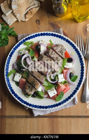 Traditional Greek salad with grilled lamb meat. - Stock Photo