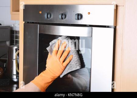 Housekeeping cleaning oven at home kitchen. Housework concept. - Stock Photo