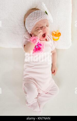 a two-month baby girl Europeans lies on his back with a bandage on his head with a flower. - Stock Photo