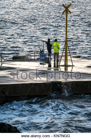 Two fishermen fishing from wet pier, North Berwick harbour, on windy cold winter day with waves splashing, East - Stock Photo