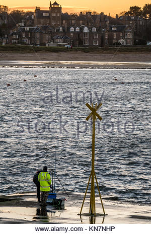 Two fishermen fishing from wet pier, North Berwick harbour, on windy cold winter day with waves splashing at sunset, - Stock Photo