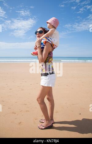 summer family of two years old blonde baby with pink hat white shirt and colorful trousers carrying on shoulders - Stock Photo
