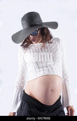 eight months brunette pregnant woman bare tummy belly button wool top sweater black sunglasses big pamela hat posing - Stock Photo